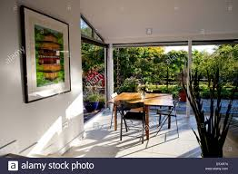 a dining room with doors that open onto a patio and garden stock