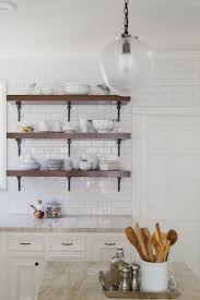 white kitchen cabinets with white countertops appliances brown three stories varnished wooden floating shelf
