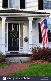 colonial home front entrance with american flag in historic stock
