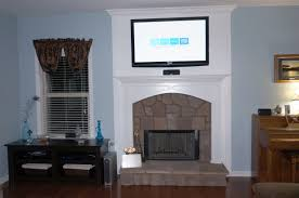 tv on the white wall panel above the brown brick fireplace placed