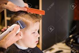 youth boy hair cut close up of man hands grooming kid boy hair in barber shop boy