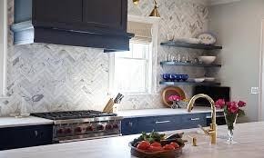 navy blue kitchen cabinets with brass bar pulls and marble chevron
