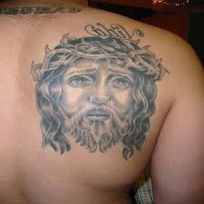sad jesus face christian tattoo on back shoulder