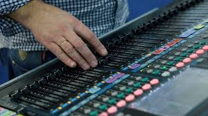 Studio Mixer Desk by A Sound Engineer Using A Mixing Desk Or Mixing Console To Mix A