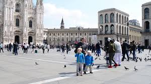 people and doves at the street of milan italy piazza vittorio
