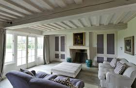 plum and ivory linen sitting room with lime washed beams poutres