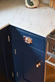 navy blue kitchen cabinet pulls combine navy cabinetry with copper handles to create sleek