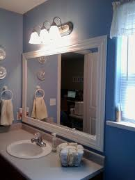 bathroom mirror frames with a small towel roll in the basket also