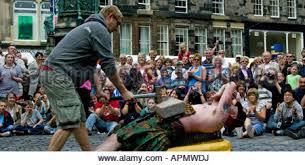 edinburgh fringe street performer lying on bed of nails being hit