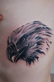 small eagle head tattoo on man chest