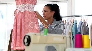 pretty fashion designer measuring the belt of a dress royalty