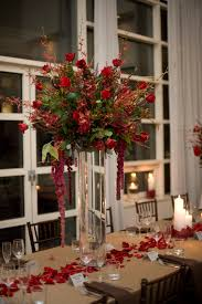 a tall centerpiece featuring red mokara orchids burgundy james