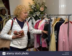 elderly woman clothes elderly woman browsing secondhand clothes stall at a macmillan