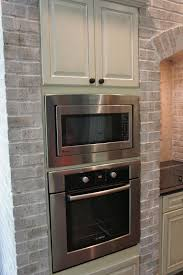 fancy white color kitchen fireplace featuring red bricks hearth