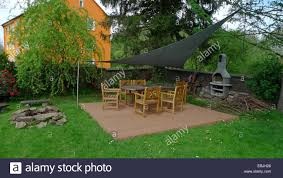 roofed garden table with many chairs in an ornamental garden stock