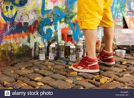 Spray Paint Artist - feet and paint cans of a spray paint artist working at the lennon