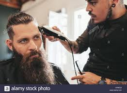 young man getting trendy haircut at salon hairstylist giving