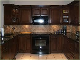 kitchen with black appliances grey blue herringbone glass mosaic
