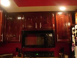 glossed mahogany wood kitchen cabinets for red wall color