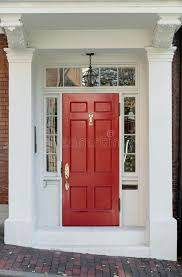 red front door with white door frame and windows on brick street