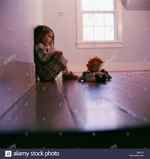 little sitting in the corner of an empty room with her