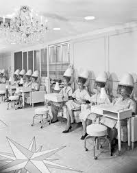 women in a beauty salon under hairdryers 1961 vintage 1960s