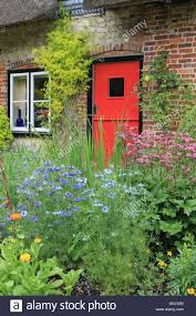 red door of a thatched cottage in english cottage garden setting
