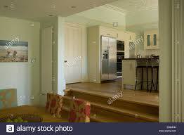 up modern kitchen modern split level dining room with steps up to kitchen area stock