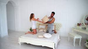young couple room loving young couple fooling around and fights pillow on bed in