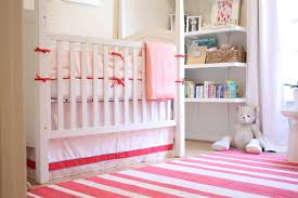 bedroom modern baby room with white crib and striped rug with