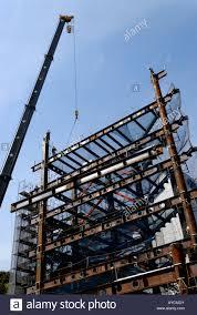 crane lifting steel beam onto high rise building under