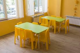 kindergarten classroom with small chairs and tables stock photo