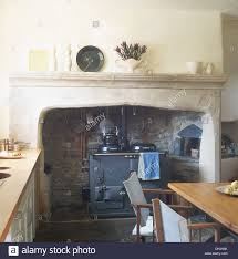aga oven in stone fireplace in country kitchen with director u0027s