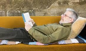 dans le canapé homme supérieur lisant un livre dans le canapé lit dehors image