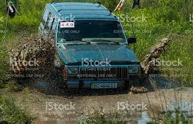 mud jeep cherokee offroad vehicle brand jeep cherokee overcomes a pit of mud stock