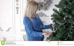 lady decorating the christmas tree with baubles and spheres stock