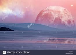 landscape of an alien planet huge pink moon reflects in calm