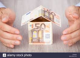 closeup of businessman u0027s hands protecting euro house on table