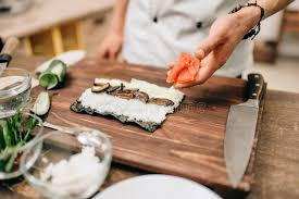 japanese restaurant cook at table male cook making sushi on wooden table asian food stock photo