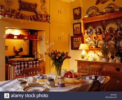 table set for tea in pale yellow country kitchen with lighting