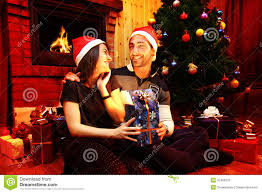 young romantic couple under the christmas tree at home with xmas