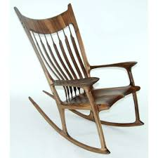 brown wooden rocking chair with bars on the back also arm rest of