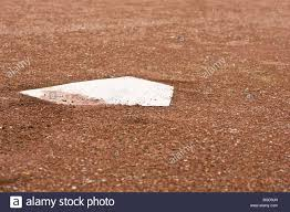 a closeup of home plate with surrounding redish brown gravel at a