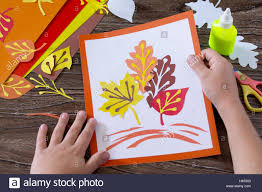 autumn leaves of colored paper on a wooden background sheets of
