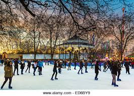 skaters on rink around bandstand in hyde park at winter stock