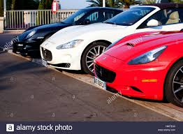 all black maserati a red ferrari a white maserati and a black porsche motor car