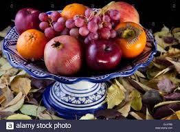 ceramic fruit bowl with autumn fruits isolated over black