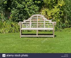 wooden garden bench on a lawn and beech hedge stock photo royalty