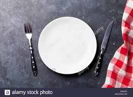 plate table top empty plate fork knife and kitchen towel over stone table top