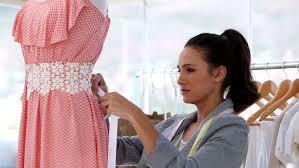fashion designer attractive fashion designer working on a dress in studio stock
